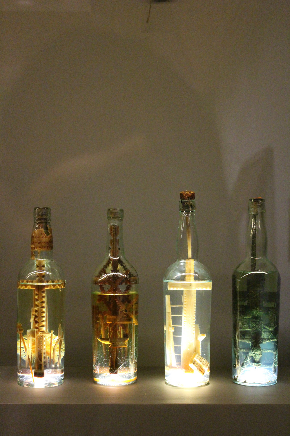 God in a Bottle (red and serrated, dark, pale, with fan-like object), 19th Century, Glass and Wood